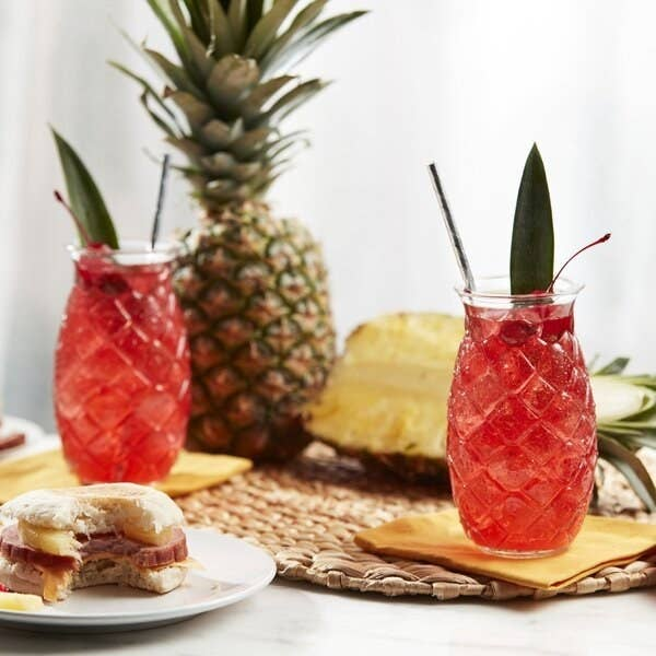 Two of the pineapple-shaped glasses, filled with juice