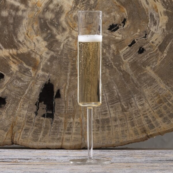 A champagne flute with a long stem and a cylindrical cup