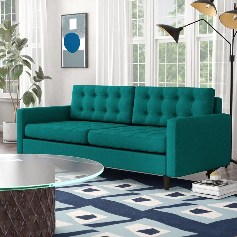 The teal tufted sofa