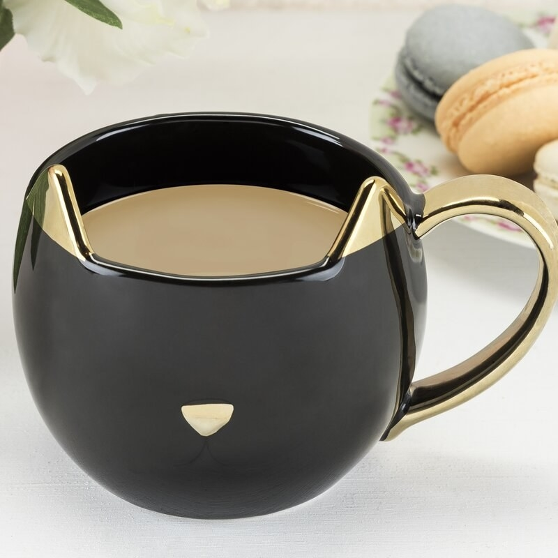 A ceramic black cat-shaped mug with gold accents and handle