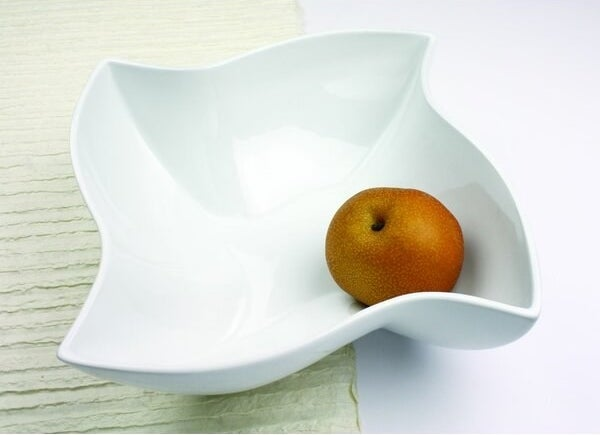 A white fruit bowl that is an abstract, pinwheel-like shape