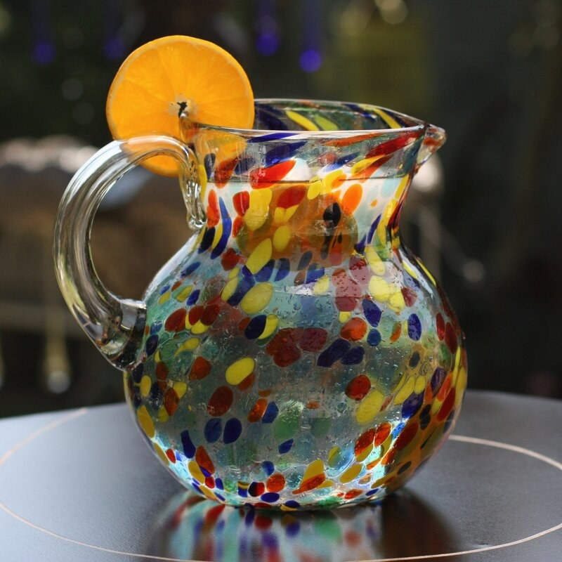 A glass pitcher with red, blue, and yellow dots in the glass