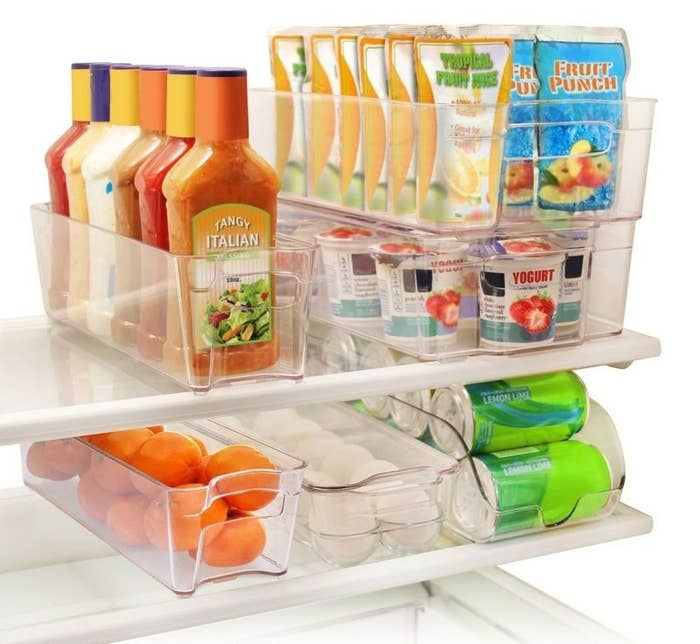 Six clear bins in a refrigerator filled with salad dressings, fruit, soda, yogurt, juice, and more