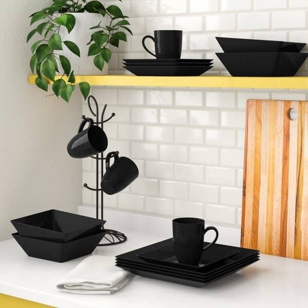 Square black plates, bowls, and mugs stacked