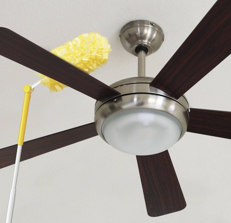 Duster wiping off ceiling fan