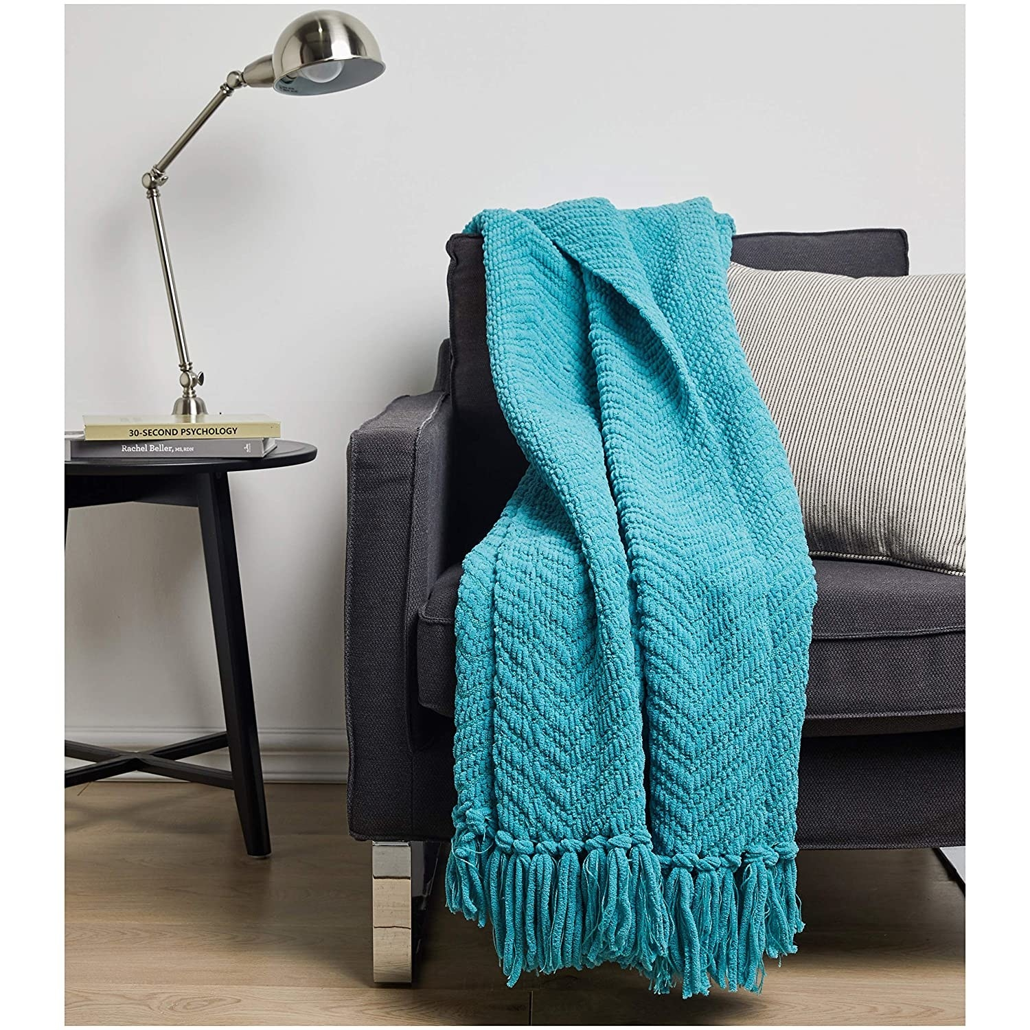A chunky teal throw draped over a black couch.