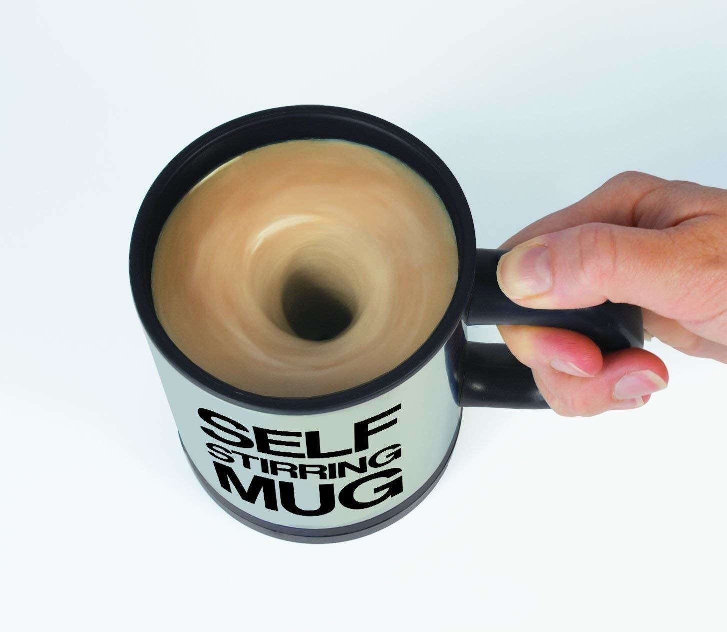 A hand holding the mug while the coffee inside is stirred.