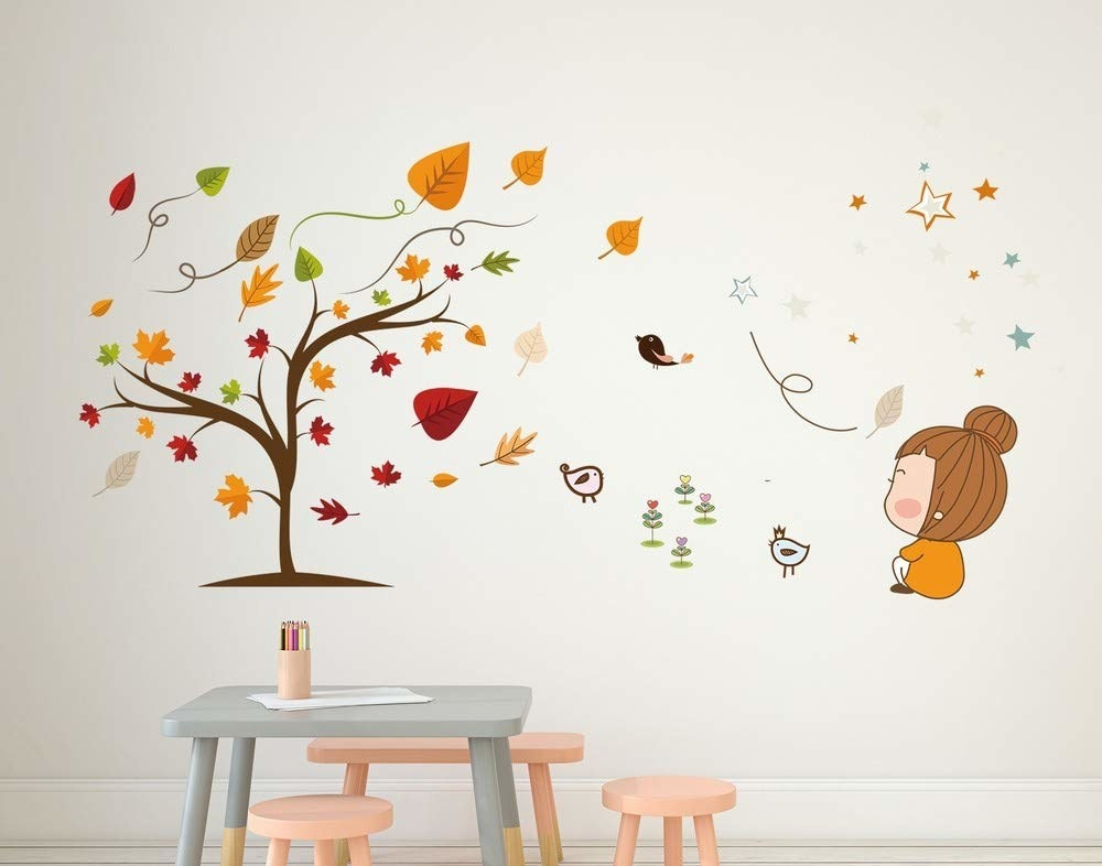 A wall decal of a shedding maple tree, a sitting cartoon figure, and doodles of birds and stars displayed on a white wall.