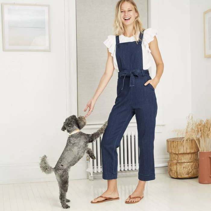Model wears overalls with white ruffled top