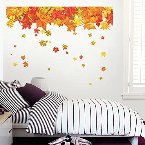 A decal of falling autumn leaves displayed on a white wall with a bed in the foreground.