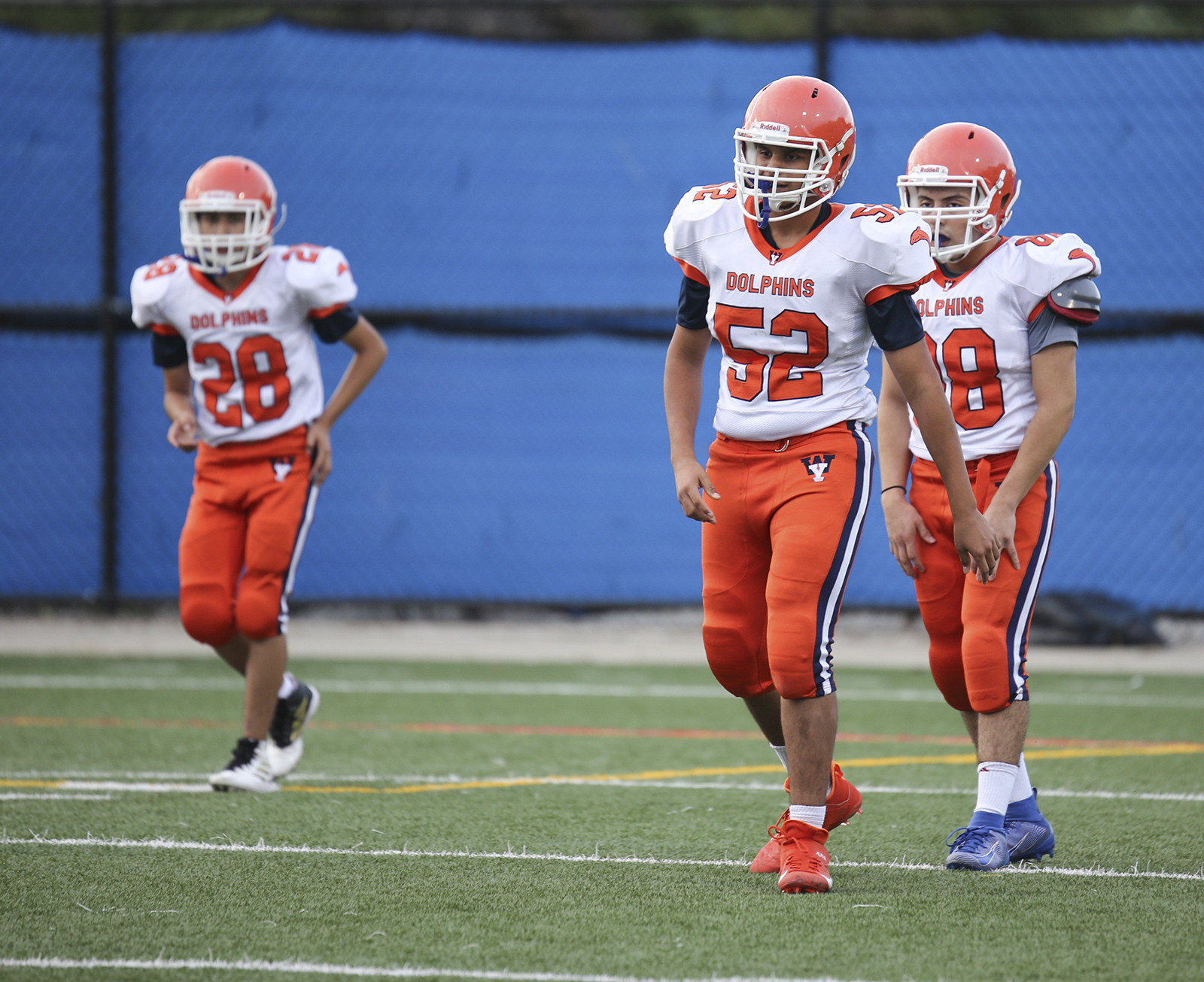 High school football players wear white-and-orange uniforms on the field