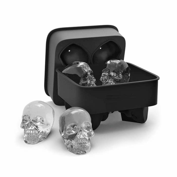 Four skull-shaped ice cubes inside and outside their black silicone container