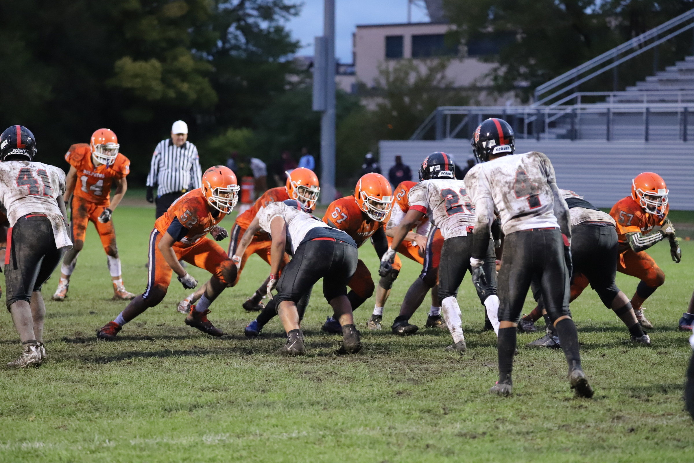 High school football players in orange and white uniforms play on a muddy field
