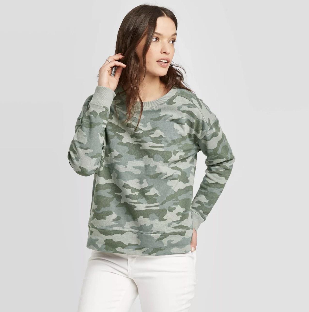 Model wearing the camo print sweatshirt