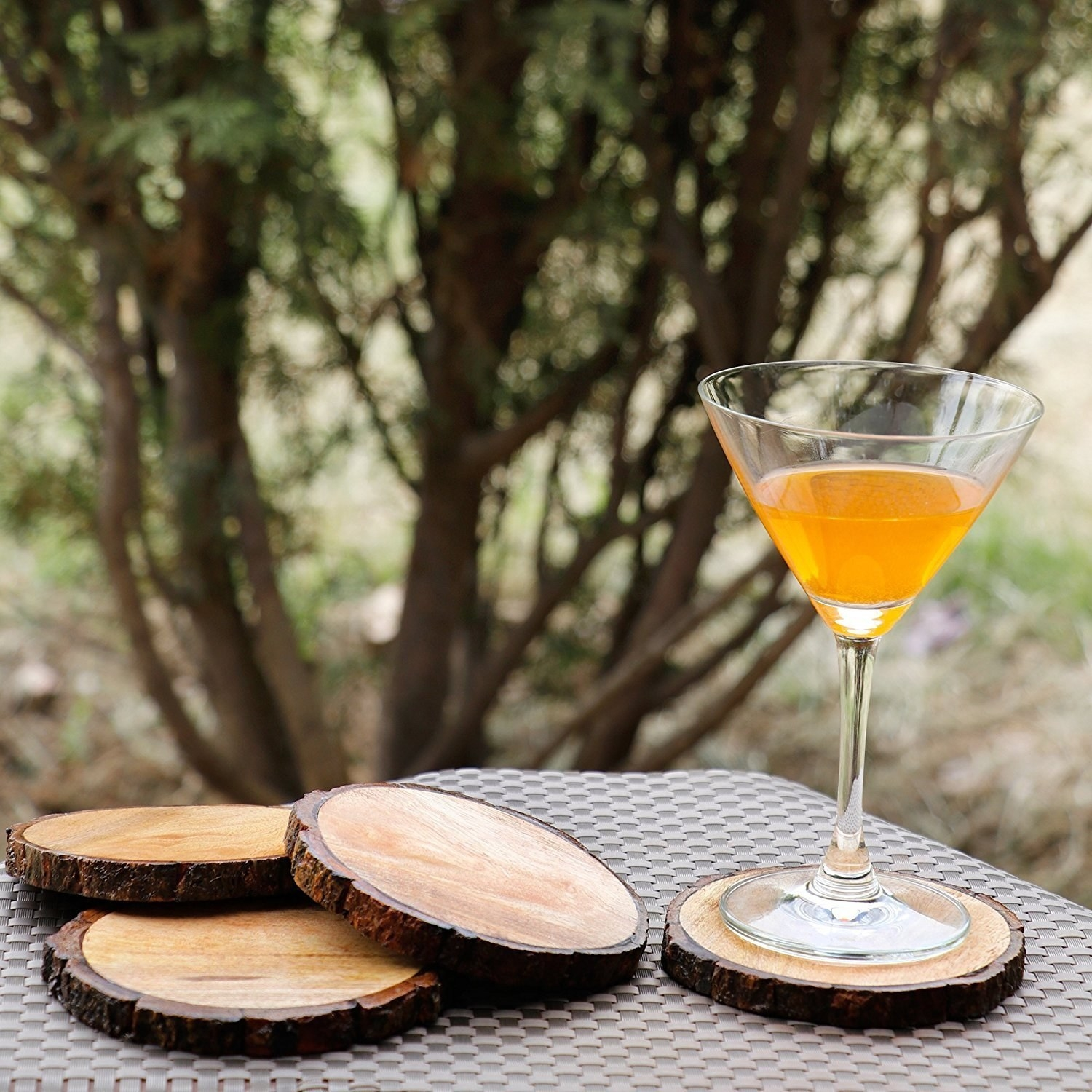 Four wooden bark coasters on an outdoor table. One has a glass with a drink placed on it