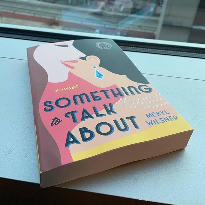 The book lying on a ledge beside a window.