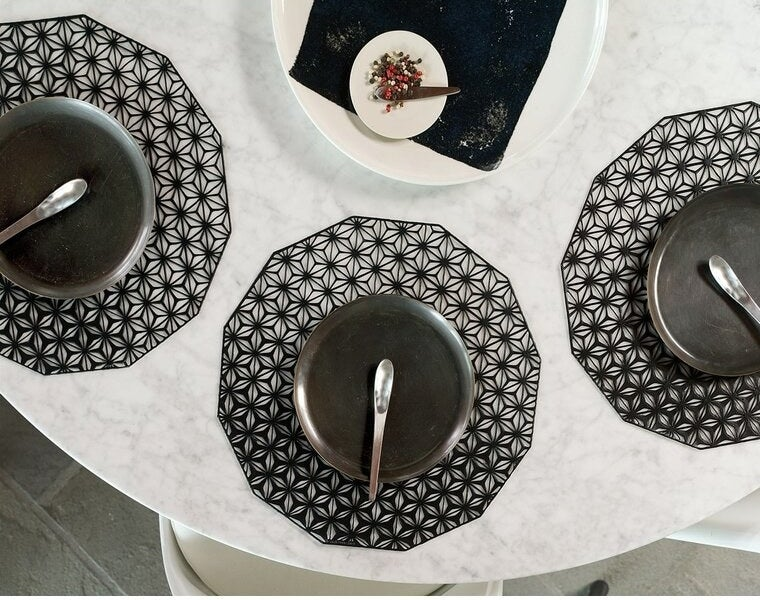 Black placemats with an abstract, cut-out design