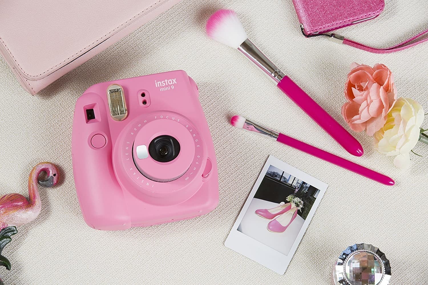 An instant camera on a table with makeup brushes and pictures