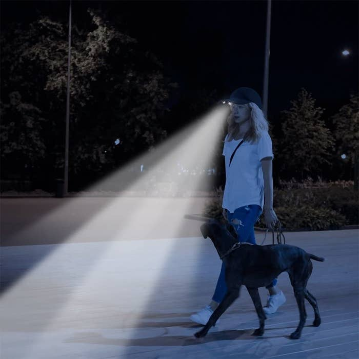 A person walks their dog with a hat that lights their way