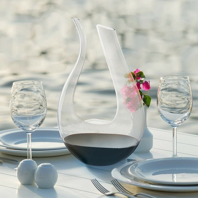 The curved glass wine decanter, with one spout for filling and one spout for pouring