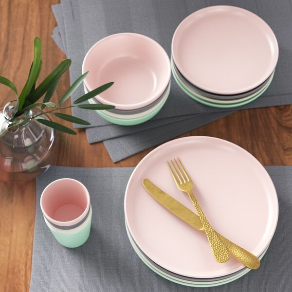 The dinnerware set, including gray, pink, and ivory plates, bowls, and cups