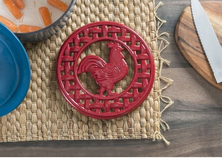 A red trivet with an image of a rooster in the middle