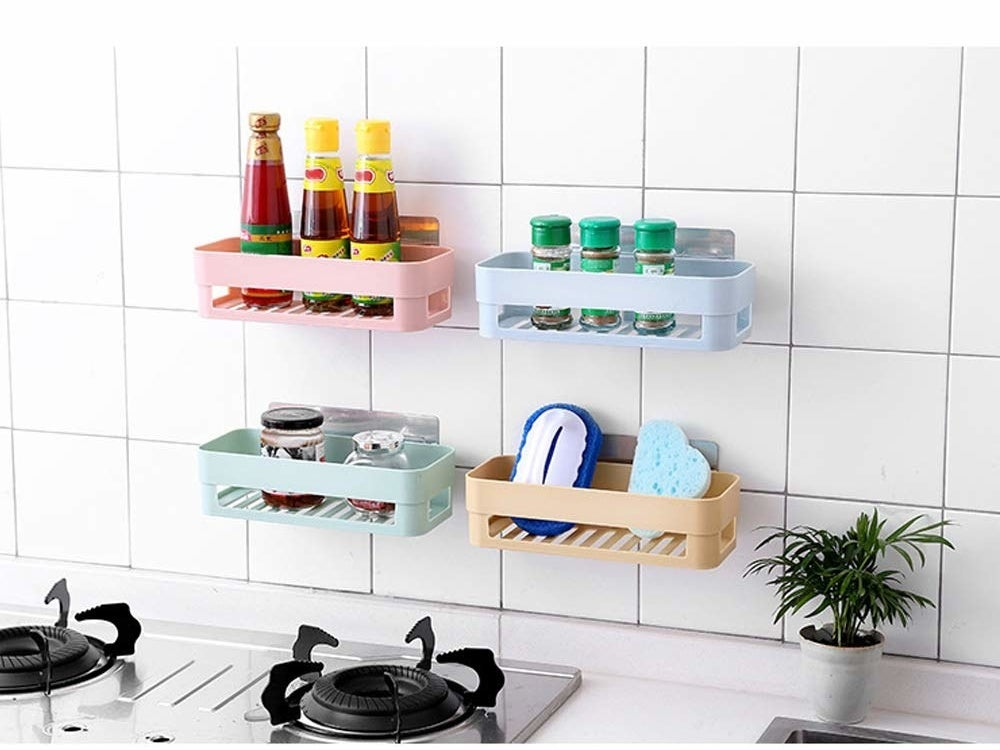 Four racks attached to the wall behind a kitchen stove and stocked with ketchup bottles, spices, glass jars, and cleaning supplies