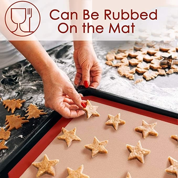 Star shaped cookies being placed on the silicone baking sheet