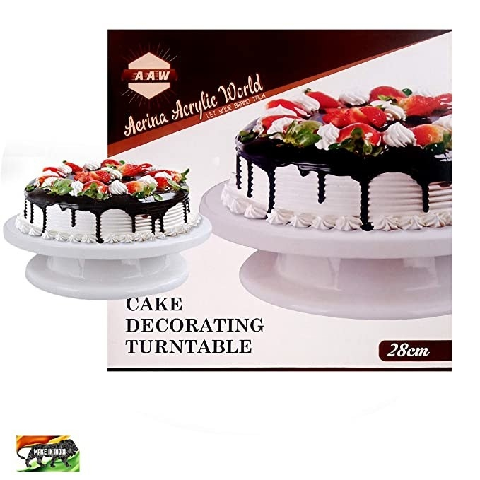 2 cake turntables with chocolate and strawberry covered cakes on them