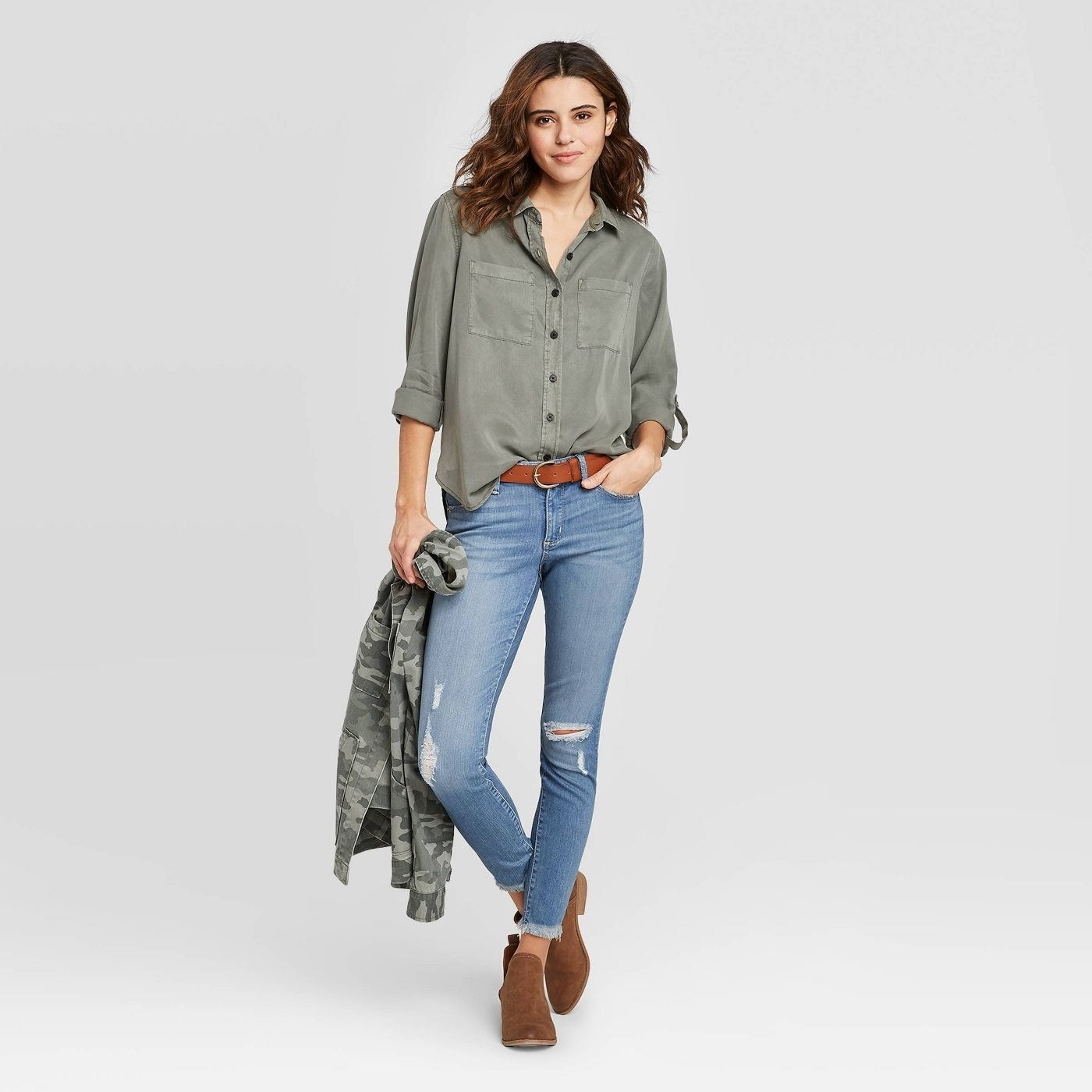Model in flowy green long sleeve button-down shirt