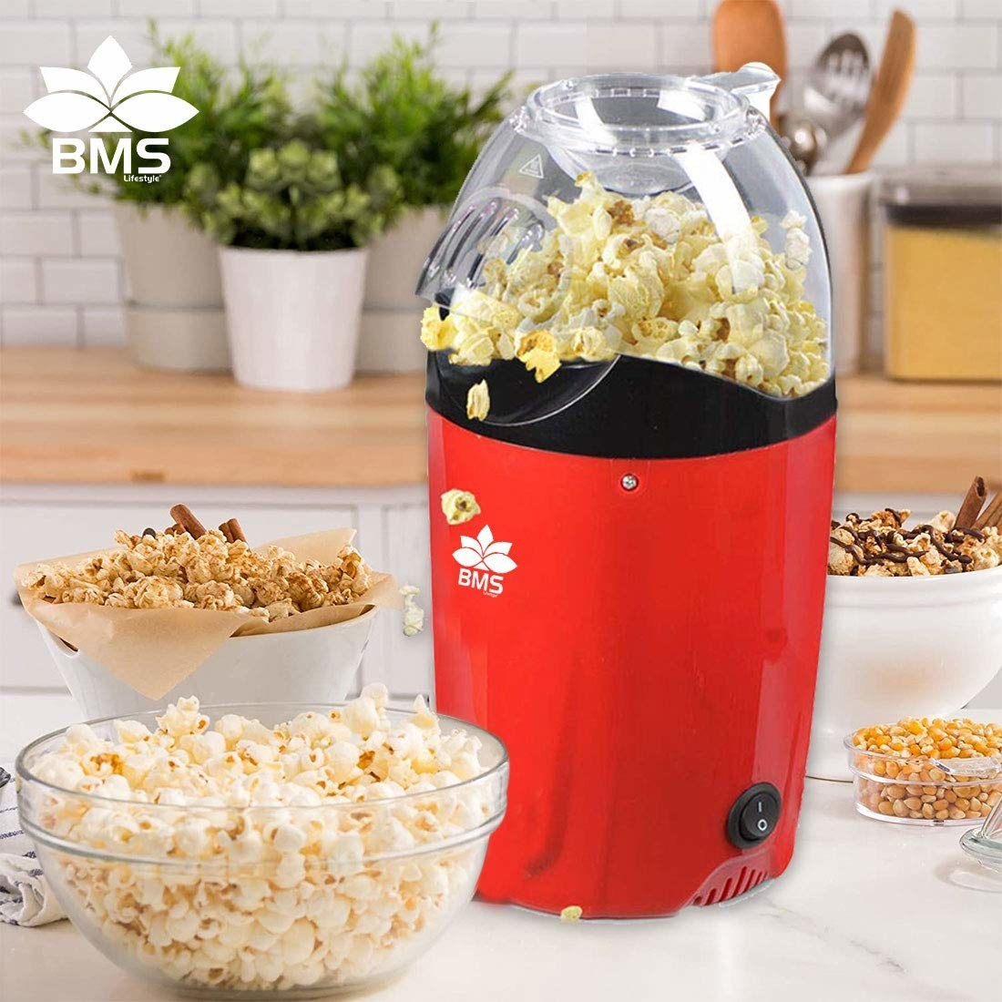 A red popcorn maker pictured while cooking the snack and a bowl of popcorn in the foreground.