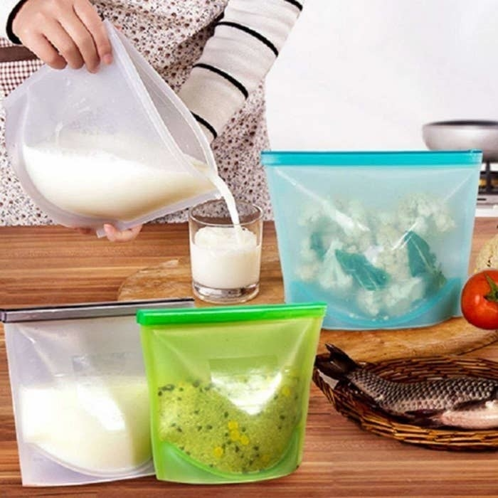 Multi-coloured silicone bags with food in them pictured with a person pouring milk out of one of the bag into a glass.