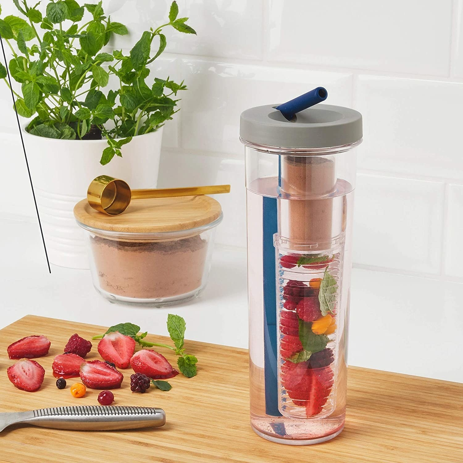 A flat lay of the infuser bottle filled with water and several varieties of berries in the infusion tube.