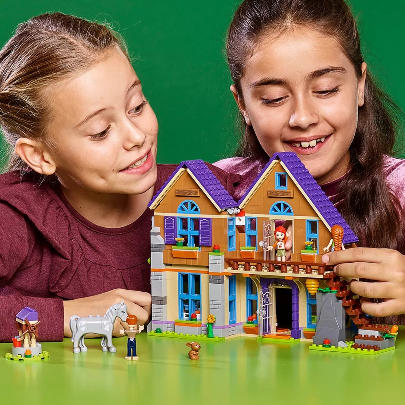 Two kids playing with dolls in the Lego doll house