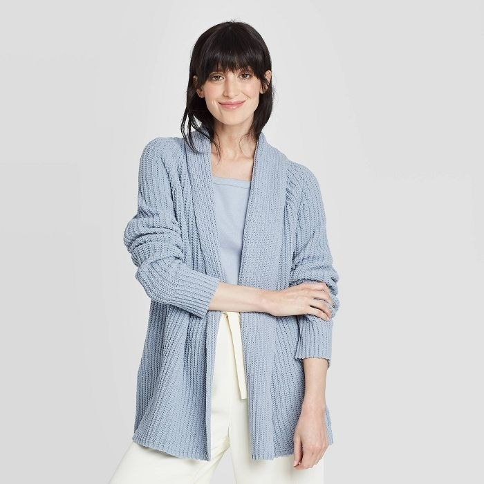 Model in open-front blue knit cardigan