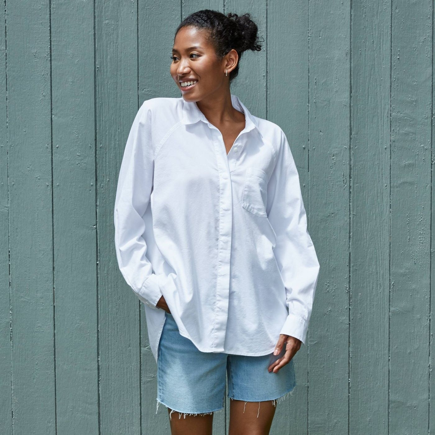 Model in oversized white button down shirt