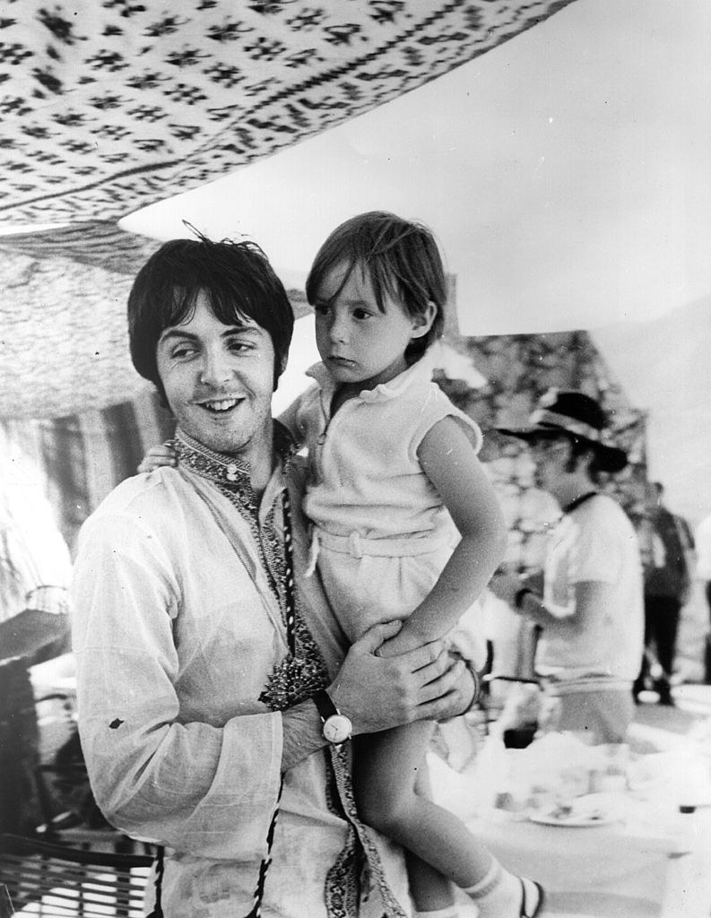 Paul McCartney holding Julian Lennon during a holiday in Greece