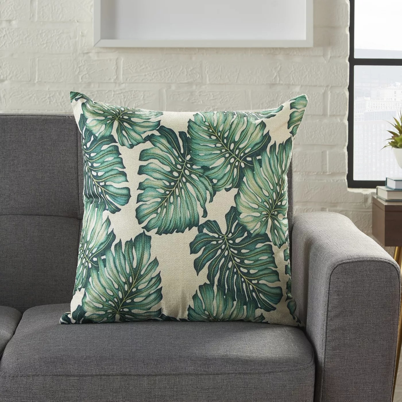 A white throw pillow with a palm leaves pattern