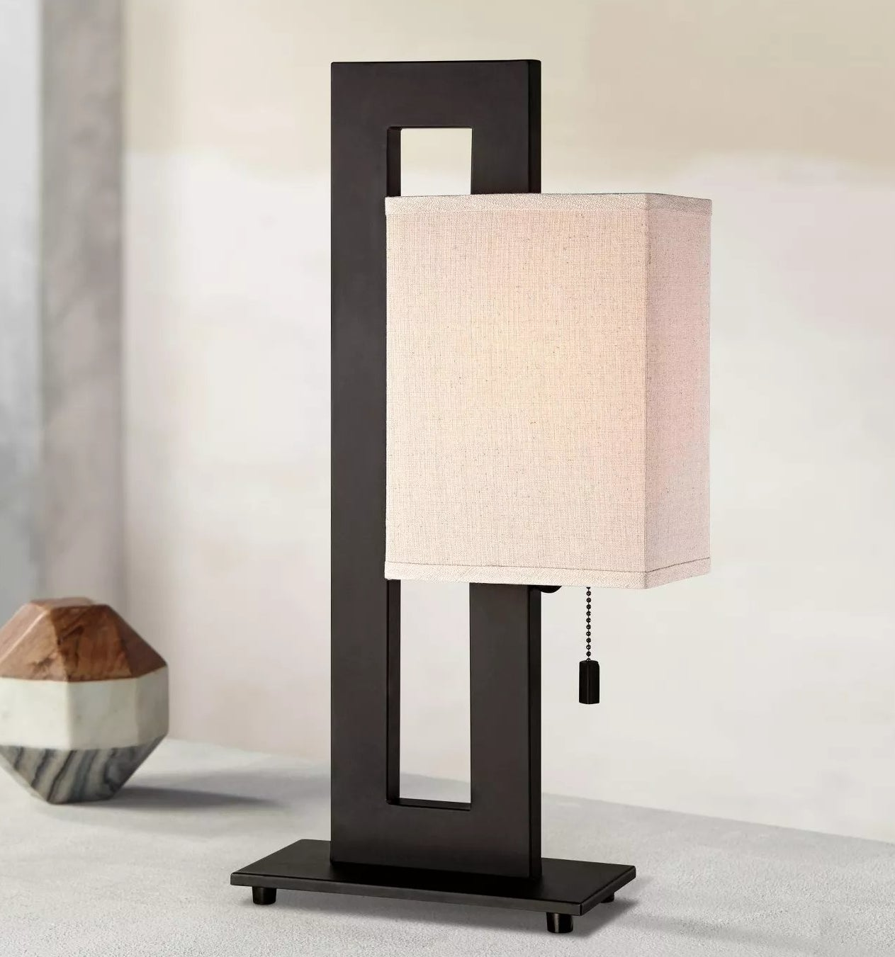 The black, asymmetrical table lamp with a beige shade