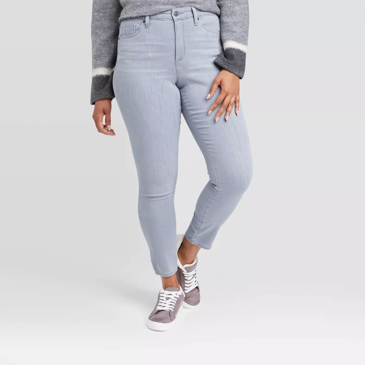 A model wearing the high-rise skinny jeans in gray