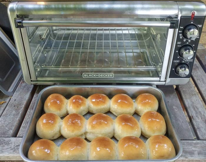 Reviewer photo of the toaster oven and a pan filled with rolls
