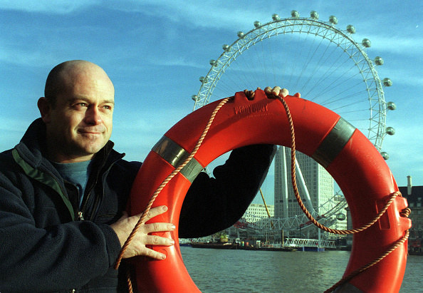 Man holding red life ring in london outside the london eye wheel