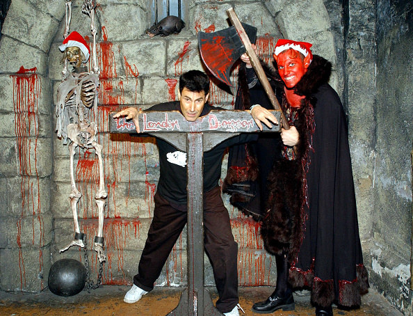 man in dungeon with man in devil costume holding an axe