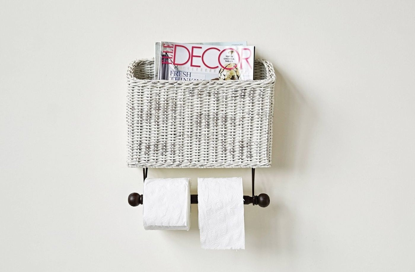 The white wicker magazine basket with black toilet paper holder