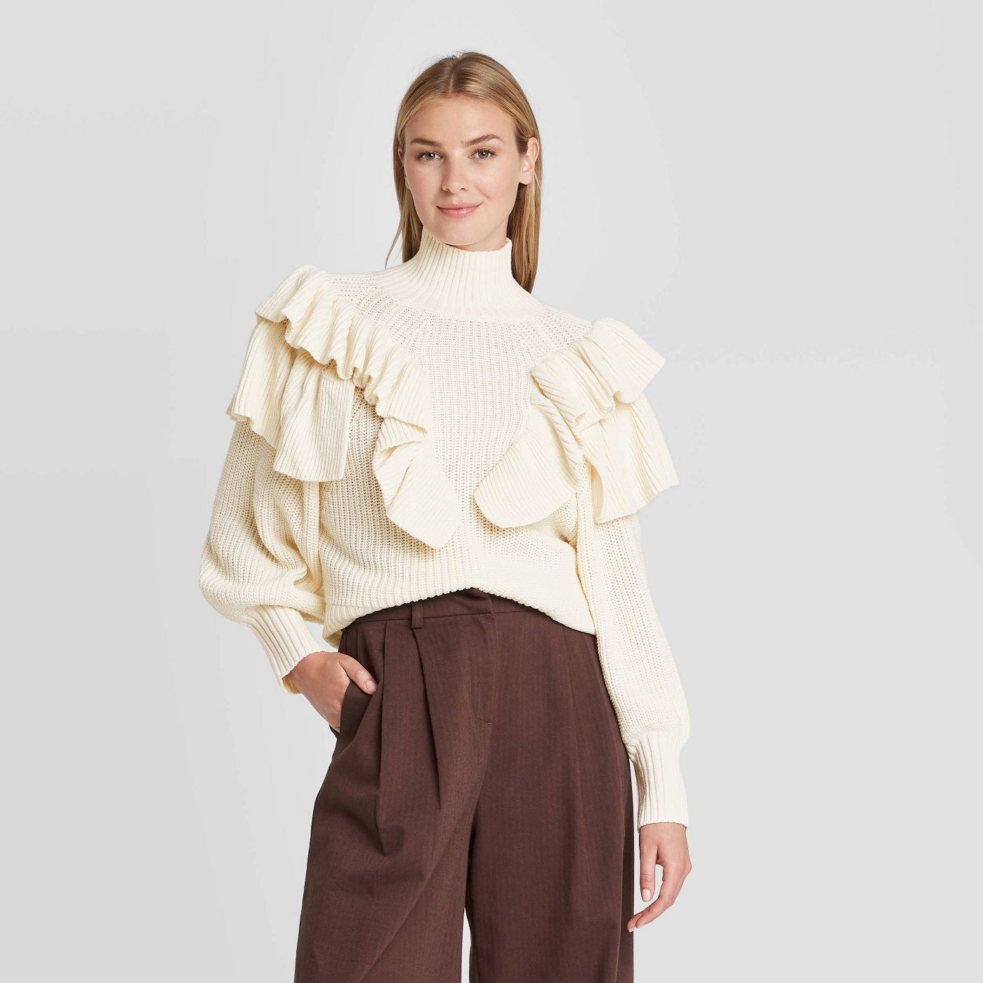 Model in cream ruffle crewneck sweater