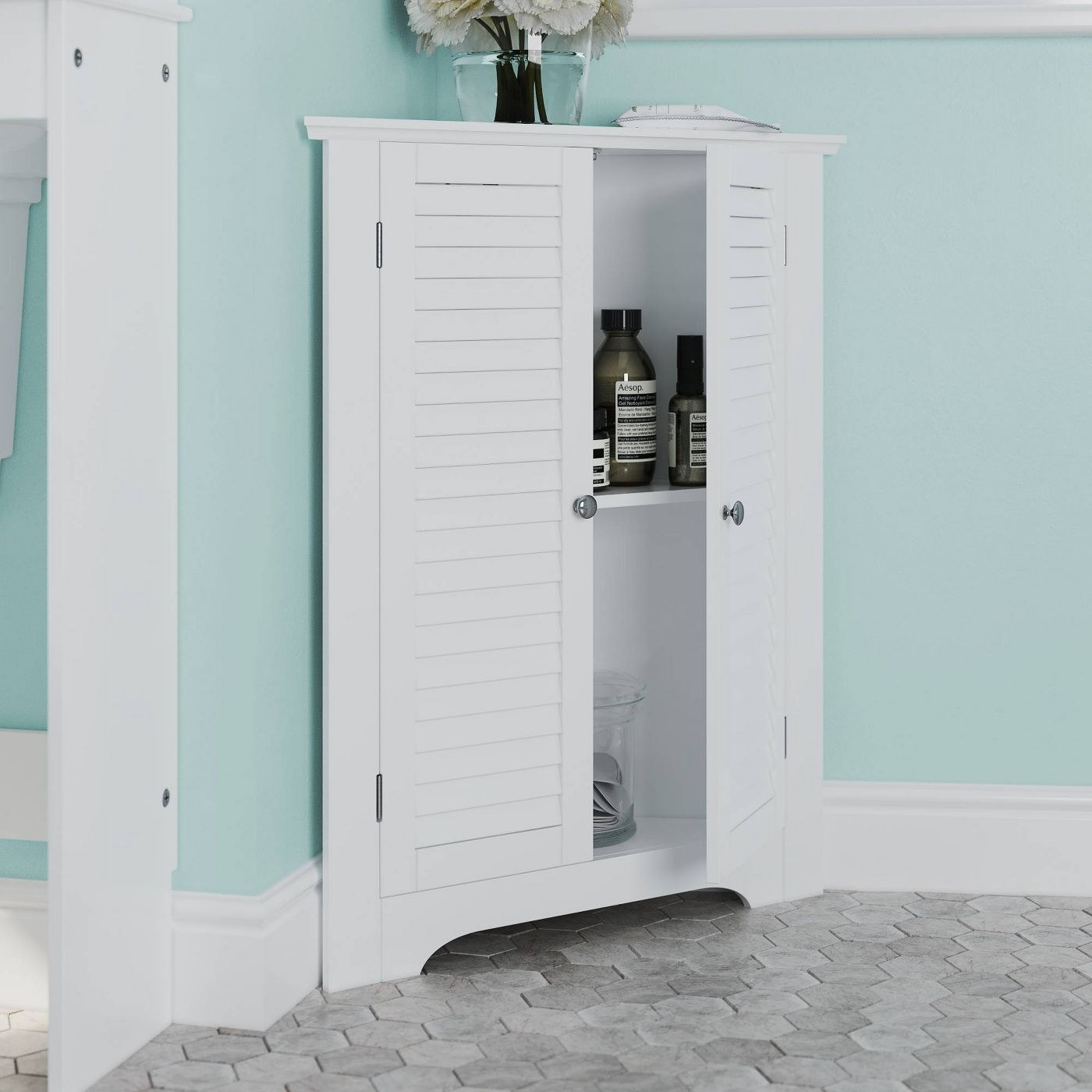 The white corner cabinet with shutter doors
