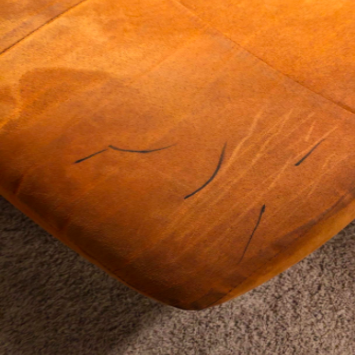 reviewer pic of brown suede couch with black sharpie marks on it