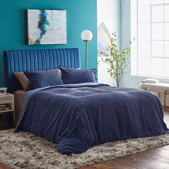 The blue duvet cover and shams on a bed