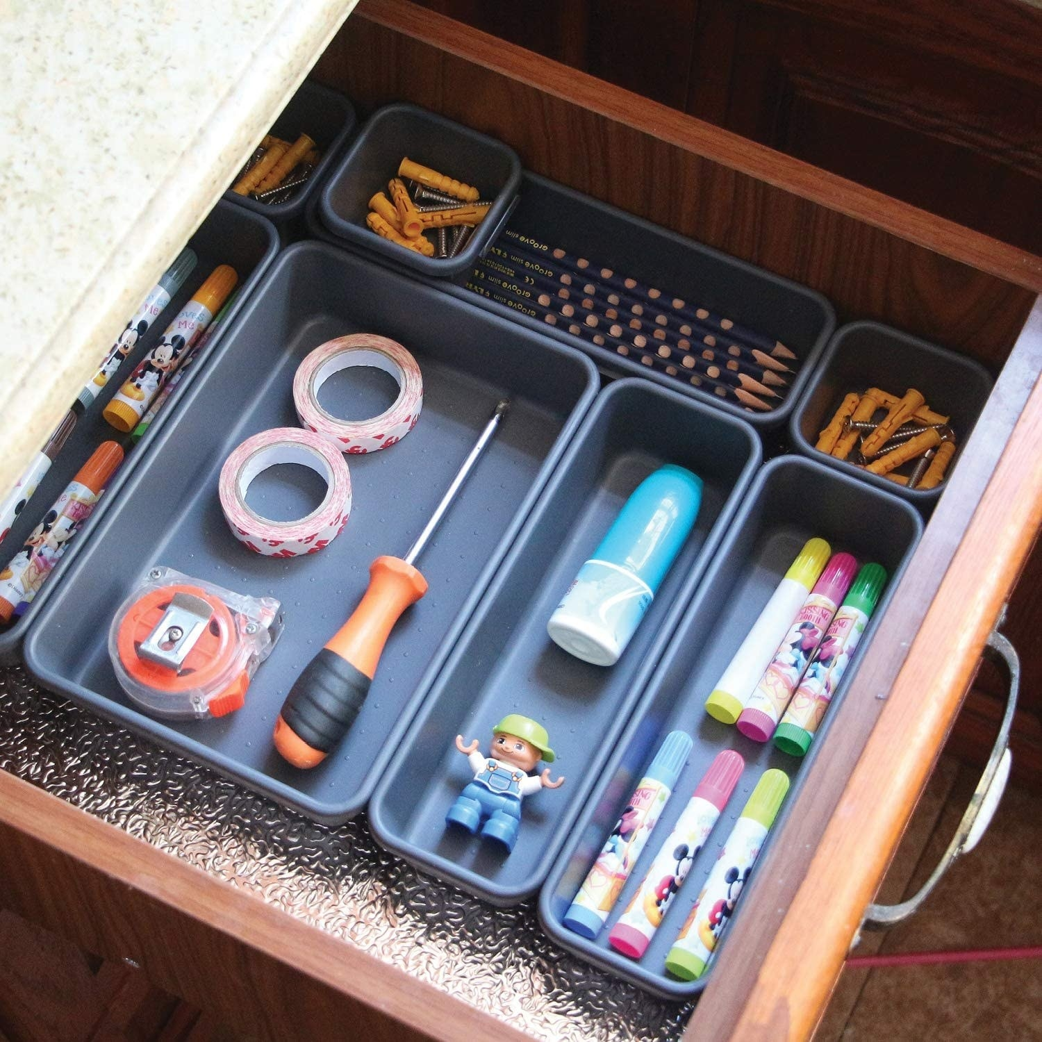 A set of gray plastic drawer organizers filled with pens, pencils, and tape