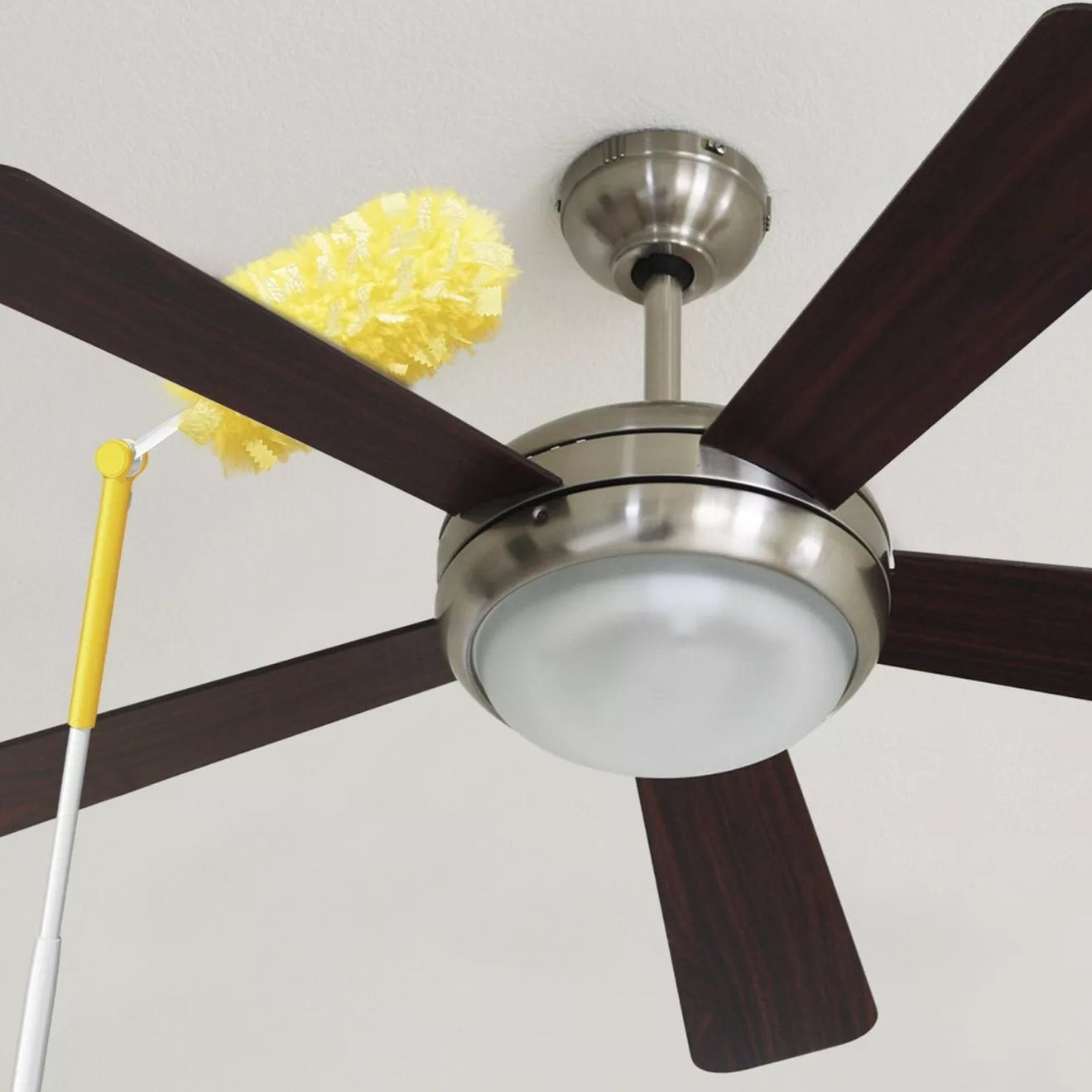 A Swiffer Duster angled to clean the top of a ceiling fan blade